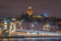 Torre de Galata y puente de Galata con las porciones de restaurante de los pescados en la escena de la noche en el cuerno de oro  imagenes de archivo