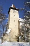 Torre de iglesia en aldea transylvanian del invierno Imágenes de archivo libres de regalías