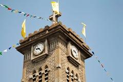 Torre de iglesia de viejo católico con una cruz y un reloj, adornados con las banderas coloridas Fotos de archivo libres de regalías