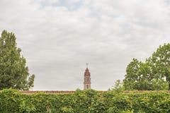 Torre de igreja atrás da parede vermelha Imagem de Stock Royalty Free
