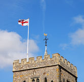 Torre de igreja inglesa da vila com bandeira Imagens de Stock Royalty Free