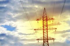 Torre de la energía en el fondo de la puesta del sol y de las nubes imagen de archivo