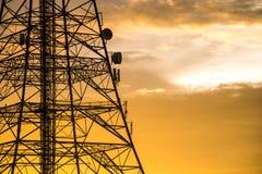 Torre de la señal en puesta del sol Foto de archivo libre de regalías