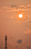 Torre de la telecomunicación con puesta del sol Imagen de archivo libre de regalías