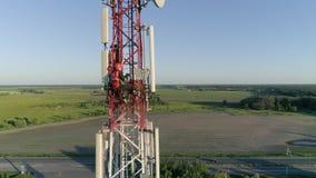 Torre de la telecomunicación del teléfono celular con el trabajador que sostiene la tableta disponible