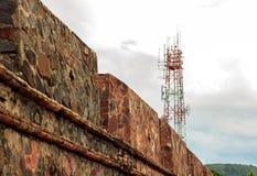 Torre de la telecomunicación, pared vieja y fondo nublado del cielo en s Foto de archivo libre de regalías