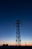Torre de la transmisión silueteada en la puesta del sol verticalmente imagen de archivo