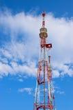 Torre de la TV en un fondo de nubes y del cielo azul Imagen de archivo libre de regalías