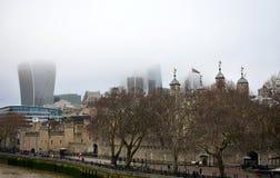 A torre de Londres e da cidade com névoa da ponte da torre Arranha-céus com névoa e caminhada de Thames River Londres, Reino Unid foto de stock royalty free