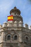 Torre De Oro在有西班牙旗子的塞维利亚 库存图片