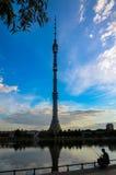 Torre de Ostankino TV contra el cielo azul y los pescados de cogida del pescador en la charca cerca, Moscú, Rusia Foto de archivo