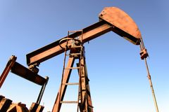 Torre de perforación de aceite oxidada vieja en luz del sol con el cielo azul Foto de archivo libre de regalías