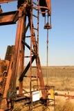 Torre de perforación de aceite oxidada vieja en luz del sol con el cielo azul Foto de archivo