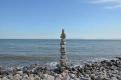 Torre de piedra en la playa fotos de archivo