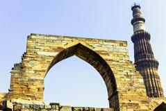 Torre de Qutb Minar vista a través la mezquita arruinada del UL-Islam de Quwwat en el complejo de Qutub Minar - Nueva Deli, la In foto de archivo