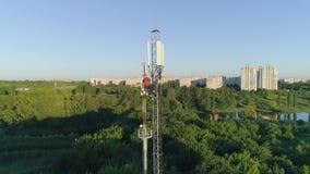 Torre de radio de mantenimiento de la telecomunicación del trabajador con el teléfono celular a disposición delante de la luz del almacen de video