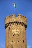 Torre de reloj con la bandera italiana del pueblo de Bagnaia Italia Imágenes de archivo libres de regalías