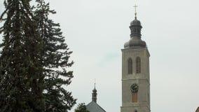 Torre de reloj europea vieja en pequeña ciudad contra el cielo nublado metrajes