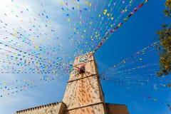 Torre de reloj, y banderas del día de fiesta en una pequeña ciudad Fotos de archivo libres de regalías