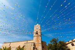 Torre de reloj, y banderas del día de fiesta en una pequeña ciudad Imagen de archivo libre de regalías