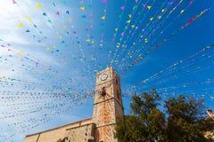 Torre de reloj, y banderas del día de fiesta en una pequeña ciudad Fotografía de archivo libre de regalías
