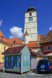 Torre de reloj y casa miniatura en Sibiu Imagenes de archivo