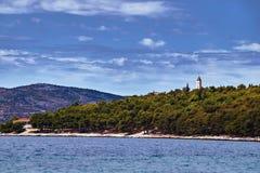 Torre de sino da floresta e da igreja na costa de mar do adriático Fotos de Stock Royalty Free