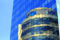 A torre de vidro redonda é refletida na construção de vidro Imagem de Stock