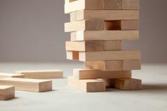 Torre dei blocchi di legno su fondo grigio Gioco da tavolo per l'intera famiglia o il partito Concetto dell'affare della costruzi fotografia stock