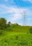 Torre del cable de transmisión en una tapa de la colina Foto de archivo libre de regalías