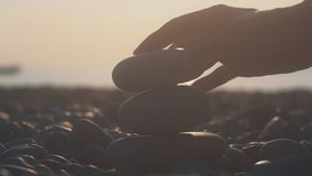 Torre del edificio de la mano de la mujer de los guijarros en la playa en la puesta del sol Relajación en la playa metrajes