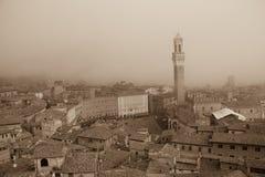 Torre del Mangia in Piazza del Campo en tupical ref-daken van Siena in de dikke mist Toscanië, Italië Oud polair effect stock foto