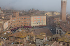 Torre del Mangia in Piazza del Campo and tupical ref roofs of Siena in the thick fog. Tuscany, Italy. royalty free stock photo