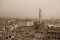 Torre del Mangia in Piazza del Campo and tupical ref roofs of Siena in the thick fog. Tuscany, Italy. Old polar effect. Stock Photo