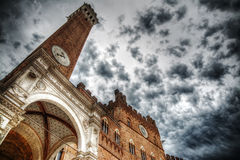 Torre del Mangia under a cloudy sky Stock Photos