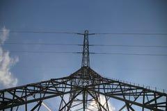 Torre del metallo per le linee elettriche in cielo blu e sole con le nuvole bianche da sotto per vedere prospettiva fotografia stock