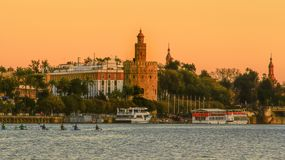 View of Golden Tower Torre del Oro of Seville, Andalusia, Spain over river Guadalquivir at sunset. The Torre del Oro English: `Tower of Gold` is a dodecagonal royalty free stock images