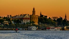 View of Golden Tower Torre del Oro of Seville, Andalusia, Spain over river Guadalquivir at sunset. The Torre del Oro English: `Tower of Gold` is a dodecagonal royalty free stock photos
