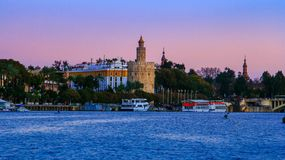 View of Golden Tower Torre del Oro of Seville, Andalusia, Spain over river Guadalquivir at sunset. The Torre del Oro English: `Tower of Gold` is a dodecagonal stock image