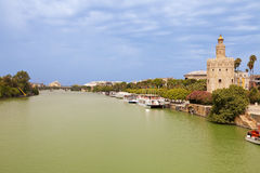 Torre del Oro over Guadalquivir river. At a cloudy summer day. Sevilla, Spain royalty free stock photo