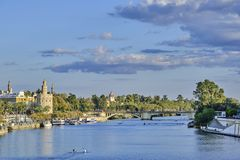 Torre del Oro of Seville and river Guadalquivir. Canoeists in the river. Bridge of `Los remedios royalty free stock images