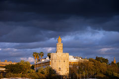 Torre del Oro in Seville at Sunset. Scenic Torre del Oro (Gold Tower) at sunset with storm clouds above, medieval landmark from early 13th century in Seville Royalty Free Stock Photo