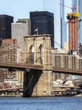 Torre del puente de Brooklyn con la bandera de los E.E.U.U., fondo de los edificios de Manhattan temprano por la mañana con brill imagen de archivo