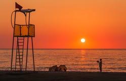 Torre del rescate del salvavidas en la playa del mar en la puesta del sol y el niño Fotografía de archivo