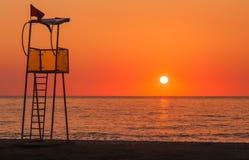 Torre del rescate del salvavidas en la playa en la puesta del sol Imágenes de archivo libres de regalías