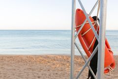 torre del salvavidas con la boya anaranjada en la playa boya del rescate en el poste del rescate del hierro fotos de archivo