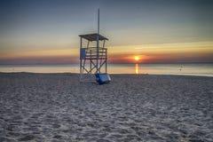 Torre del salvavidas en la playa en la salida del sol Fotos de archivo libres de regalías