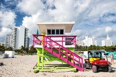 Torre del salvavidas y coche de madera del jeep en la playa arenosa Imagen de archivo libre de regalías
