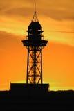 Torre del teleférico de Montjuic en la puesta del sol Imagen de archivo libre de regalías