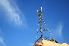 Torre del teléfono celular en el edificio contra el cielo azul Imagen de archivo